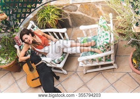 Beautiful Woman Caressing Her Dog And Playing Guitar Outdoors.