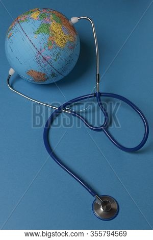 Vertical View Of Terrestrial Globe With A Stethoscope On Blue Background