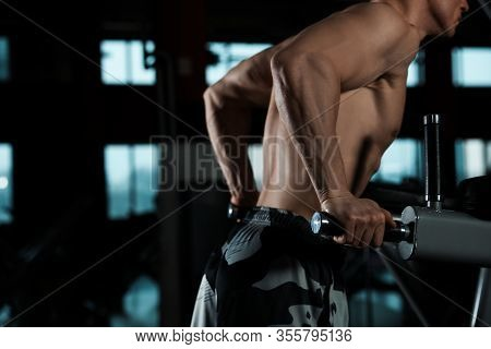 Strong Man Working Out On Parallel Bars In Modern Gym, Closeup