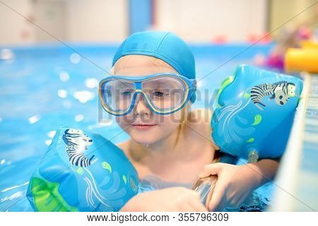 Little Boy With Glasses And Inflatable Armbands In Swimming Pool. Child Learning To Swim.