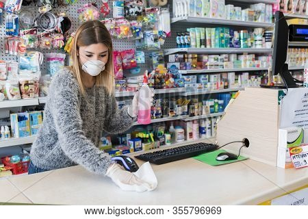 Avetrana, Italy, - Marth, 13, 2020. Saleswoman Cleaning Counter With Disinfectant Liquid With Alcoho