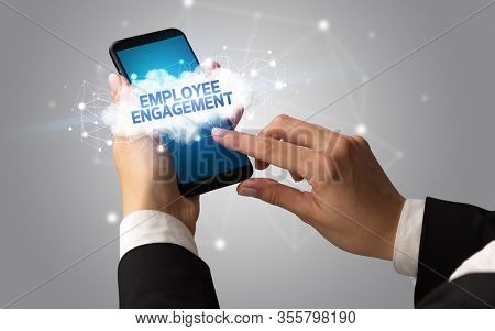 Female hand touching smartphone with EMPLOYEE ENGAGEMENT inscription, cloud business concept
