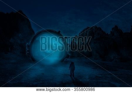 Man Standing In Front Of Dimensional Gate. Futuristic Landscape At Night. Mountains At Background.