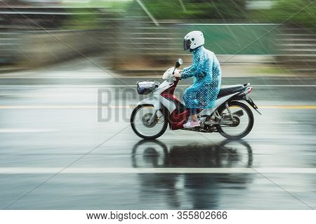 Motorcycle Raincoat In The Rain,people Drive Motorbike In Rain Day,motion Blur Of Rush On Running St