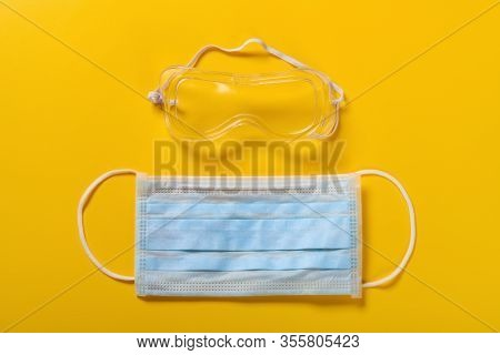 Medical Face Mask And Eye Protector On Yellow Background