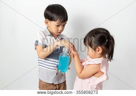Boy And Girl Using Alcohol Antiseptic Gel For Cleaning Hands To Prevent Against Infection Of Covid-1