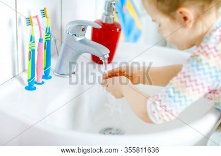 Closeup Of Little Toddler Girl Washing Hands With Soap And Water In Bathroom. Close Up Child Learnin