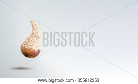 Oatmeals Flakes Flying Out From Wooden Bowl To Grey Background. Banner Format. Copy Space. Healthy B