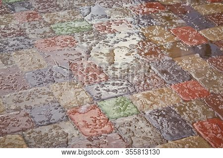 Sidewalk Tiles Covered With And Ice.background Of A Snow-covered Sidewalk Close-up