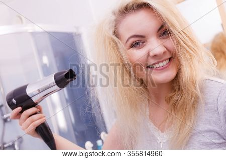Haircare. Beautiful Long Haired Blonde Woman Drying Hair In Bathroom. Smiling Girl Blowing Wind On W