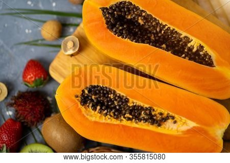 Papaya. Tropical Fruits. Close Up Shot Of Two Halves Of Ripe Papaya With Seeds On Wooden Cutting Boa