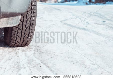 A Car Wheel On A Slippery Winter Road. Close- Up Of Studded Rubber On Ice. Dangerous Driving Conditi