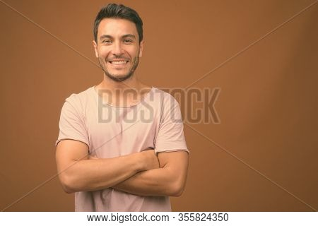 Young Handsome Hispanic Man Against Brown Background