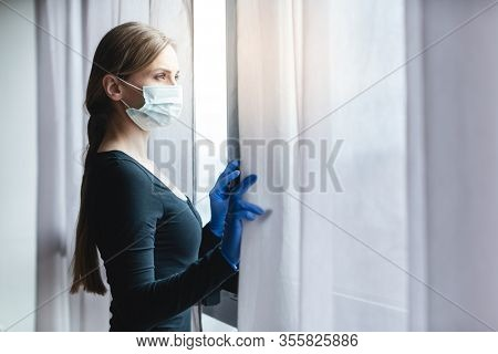 Bored woman in corona quarantine looking out of window to the street