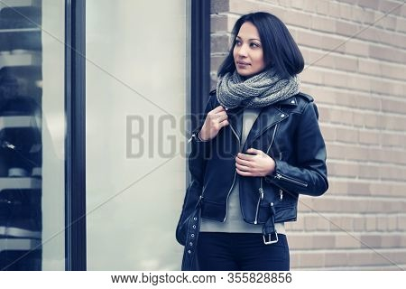 Young fashion woman looking at mall window Stylish female model in black leather jacket and gray snood scarf