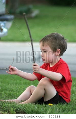 Young Boy Playing With Sticks