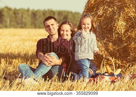 Happy young family with two year old baby girl next to hay bales in harvested field