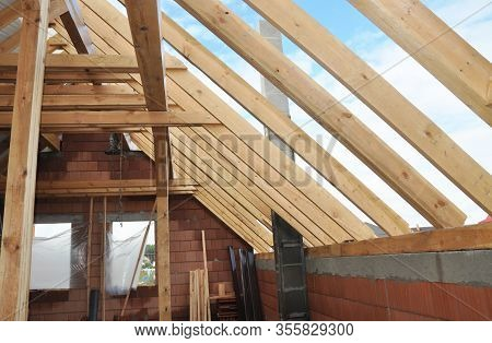 Attic Roof Beams Against Blue Sky. Constructing Rooftop Frame From Wooden Beams. Attic Under Constru