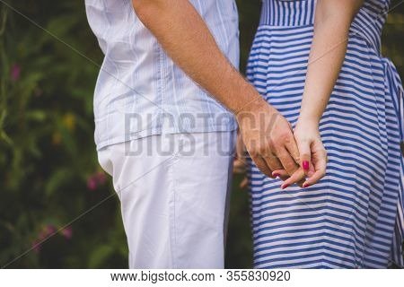 A Man And A Woman Are Holding Hands While Walking In A Park On A Sunny Day. A Love Couple Spends Tim