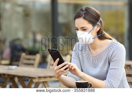Serious Woman With Protective Face Mask Looking At Smart Phone Checking News On A Cafe Terrace