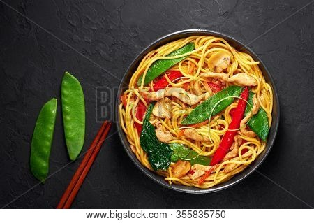 Chicken Lo Mein In Black Bowl At Dark Slate Background. Lo Mein Is Chinese Cuisine Dish With Chicken