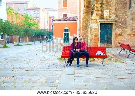 Multiracial Tourist Couple, Asian Caucasian,  In Early Fifties Sitting Together On Red Bench In Empt