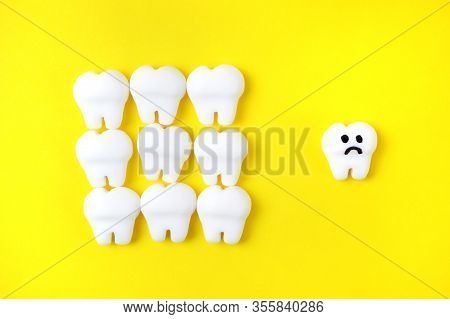 Caries Concept With White Models Of Teeth And One Sad Tooth