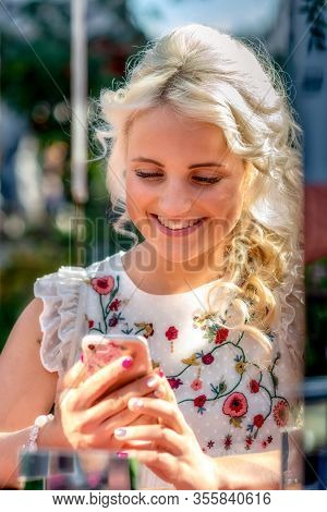 A Young, Sympathetic, Blonde Woman Using A Smartphone, Portrait Of A Woman Through A Mirror Installa