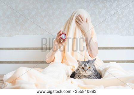 Difficult Early Waking Up In The Morning Concept With Woman Under The Blanket Holding The Alarm Cloc