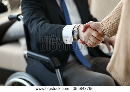 Close-up View Of Co-workers Shaking Hands. Businesswoman And Disabled Colleague On Wheelchair. Busin