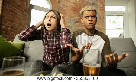 Emotional. Excited Couple, Friends Watching Sport Match, Chsmpionship At Home. Multiethnic Friends,