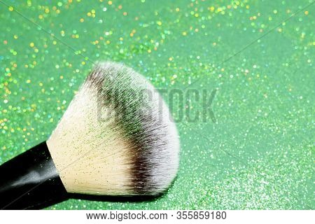 Powder Brush With Green Shimmer Shadows For St.patricks Day Makeup In The Left Corner On A Green Gli