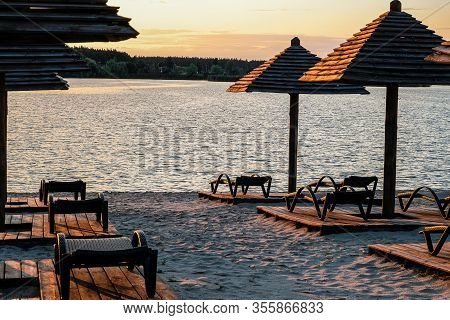 Evening Sandy Beach With Brown Wooden Loungers And Umbrellas. Empty Rows Resting Places. Recreation