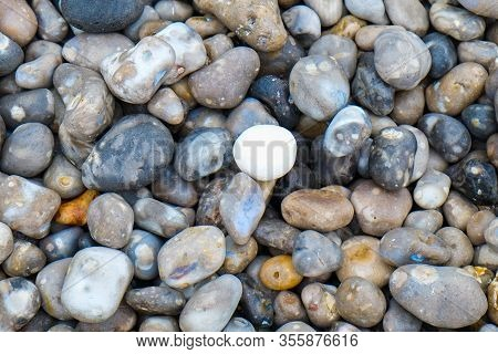 Close Up Of The Pebbles On A Beach In Normandy France, Creating An Abstract Smooth Round Pebbles Sea