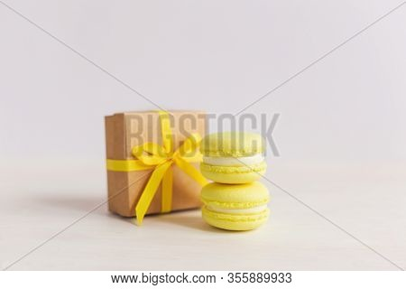 Yellow Macarons With Gift Box On A White Wooden Background. Lemon Macarons. Place For Text.