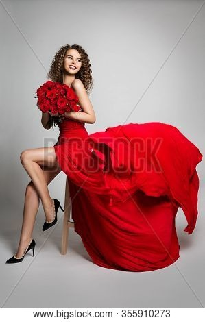 Woman With Flowers Roses In Red Dress Flying On Wind, Beautiful Fashion Model Studio Portrait In Flu