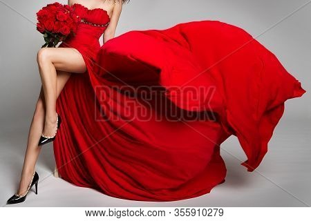 Sexy Woman Legs And Flowers Roses, Red Dress Flying On Wind, Beautiful Girl Studio Portrait In Flutt