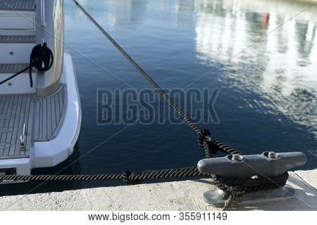 Gray Metal Mooring Post With A Black Knotted Rope In Front Of The Blue Water With A Moored Boat In A