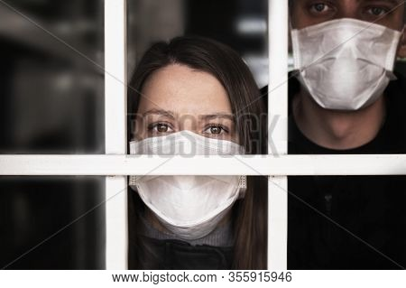 A Woman In A Mask , Looking Intently At The Camera. Quarantine And Isolation Of Patients With Covid
