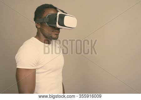 Young Handsome African Man Using Virtual Reality Headset Against Gray Background