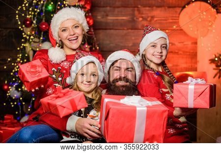Parents And Children Opening Christmas Gifts. Father Santa Claus And Mother Little Daughters Christm