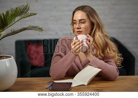 Female In Glasses, Pink Cardigan. Holding A Cup, Sitting At Wooden Table With A Tablet, Notebook And