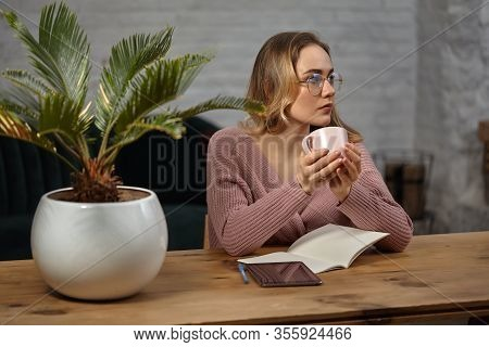 Woman Glasses, Pink Cardigan. Holding A Cup, Sitting At Wooden Table With A Tablet, Notebook And Flo