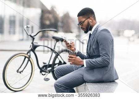 People, Technology And Lifestyle Concept. Black Man In Specs And Headphones Using Smartphone, Drinki