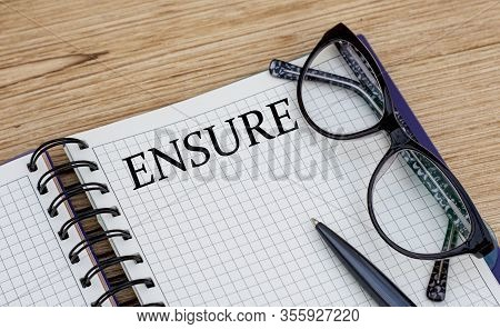 The Word Ensure Is Written In A Notebook With Glasses
