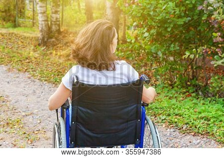 Young Happy Handicap Woman In Wheelchair On Road In Hospital Park Enjoying Freedom. Paralyzed Girl I