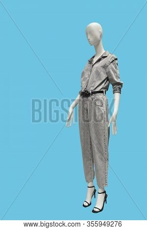 Full Length Female Mannequin Dressed In Gray One-piece Suit, Isolated On Blue Background. No Brand N