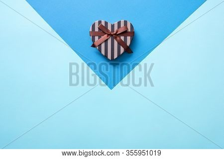Heart shaped Valentines Day gift box on a blue. Top view holiday background.