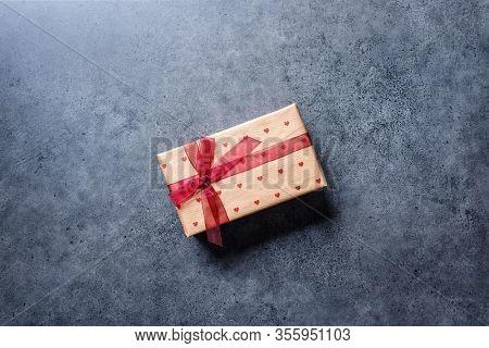 Valentine's Day gift box on a dark concrete desktop. Top view.