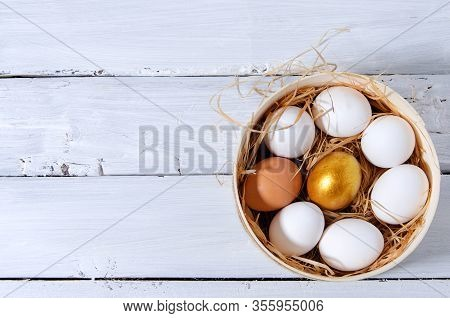 Easter Background. In A Sieve In The Hay There Are White Chicken Eggs, One Golden Egg, One Brown. A